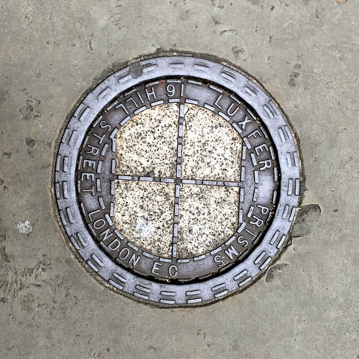 Manhole Cover, London - Cast iron surround inscribed with Luxfer Prisms 16 Hill Street London EC - Concrete centre divided into four sections