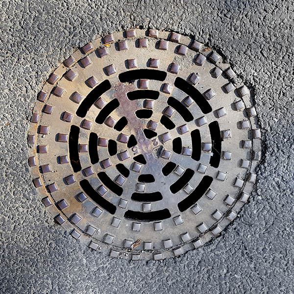 Manhole Cover, London - Cast iron raised squares and openwork circular grid