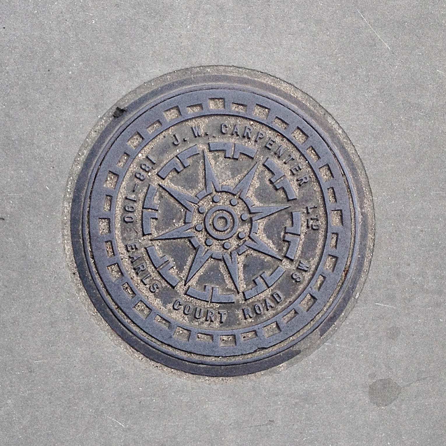 Manhole Cover, London - Cast iron surround inscribed with J W Carpenter Ltd 188-190 Earls Court Road SW - Inner star pattern