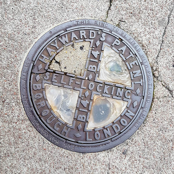 Manhole Cover, London - Cast iron with four glass inserts and text