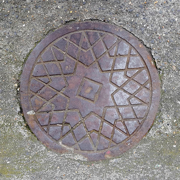 Manhole Cover, London - Cast iron criss cross star pattern with square in the centre