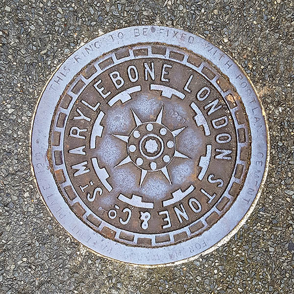 Manhole cover, London - Cast iron star surrounded by wording St MARYLEBONE LONDON STONE & Co