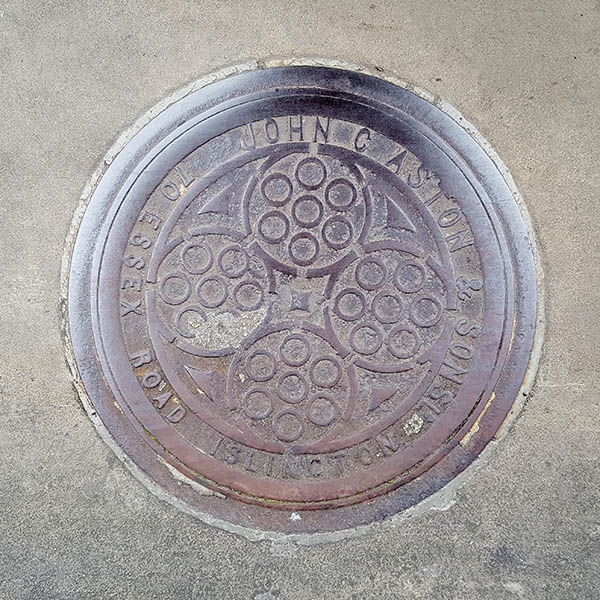 Manhole Cover, London - Cast iron surround inscribed with John C Aston & Sons 70 Essex Road Islington - Inner pattern of four circles surrounding smaller circles