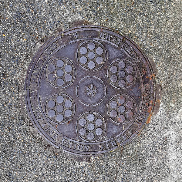 Manhole Cover, London - Cast iron surround inscribed with Hayward Brothers 187 & 189 Union Street Borough - Inner pattern of six circles surrounding smaller raised circles