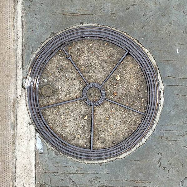 Manhole Cover, London - Cast iron surround with concrete centre, divided into five segments