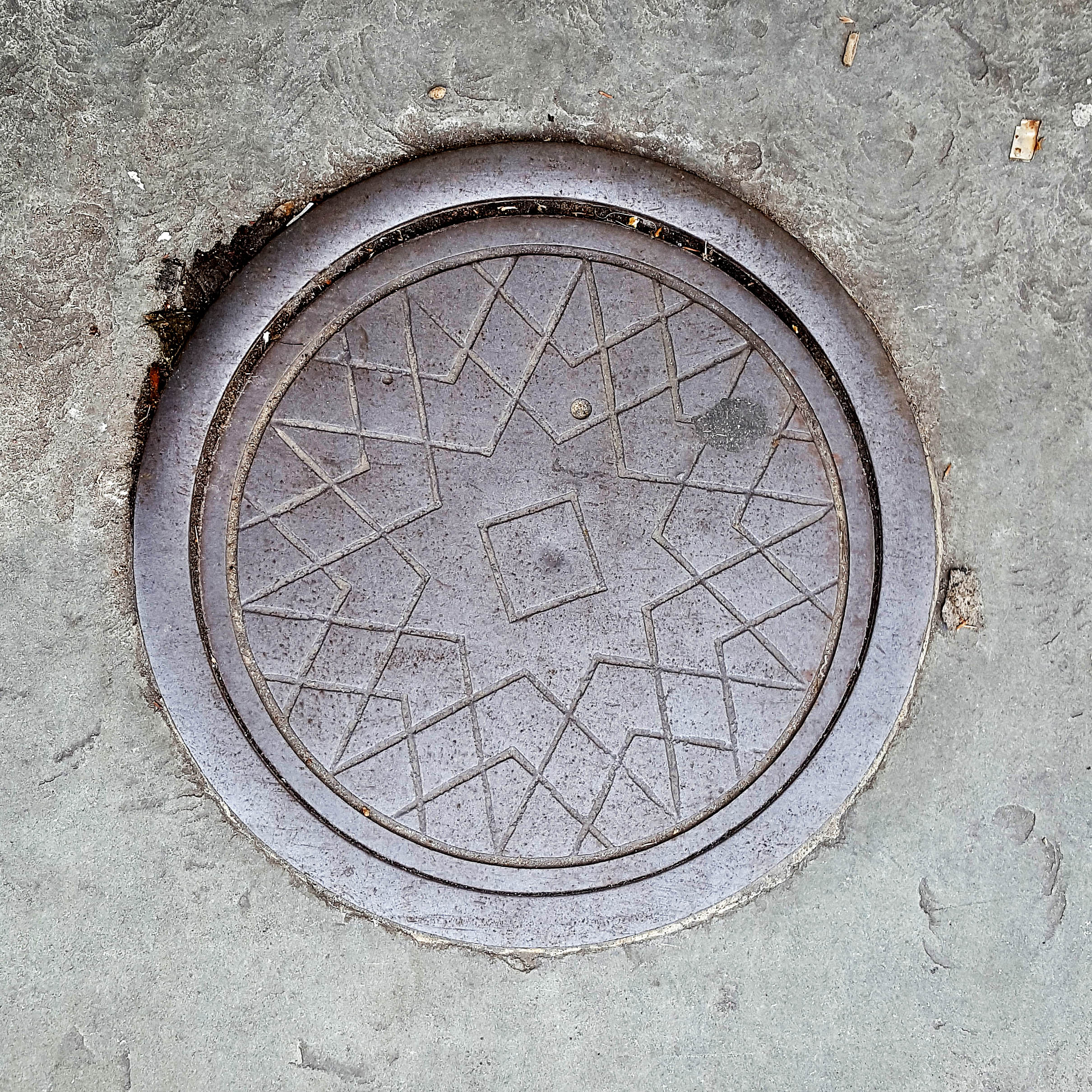 Manhole Cover, London - Cast iron surround with criss cross star pattern and square in the centre