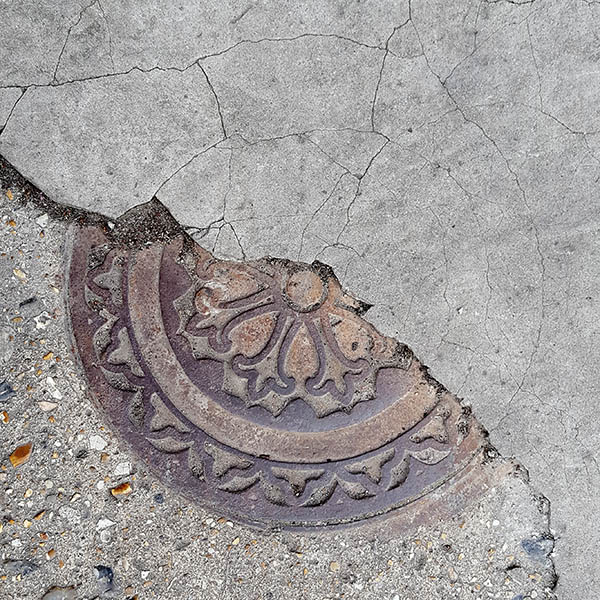 Manhole Cover, London - Cast iron with decorative circular fleur dis lis pattern half covered in concrete - London