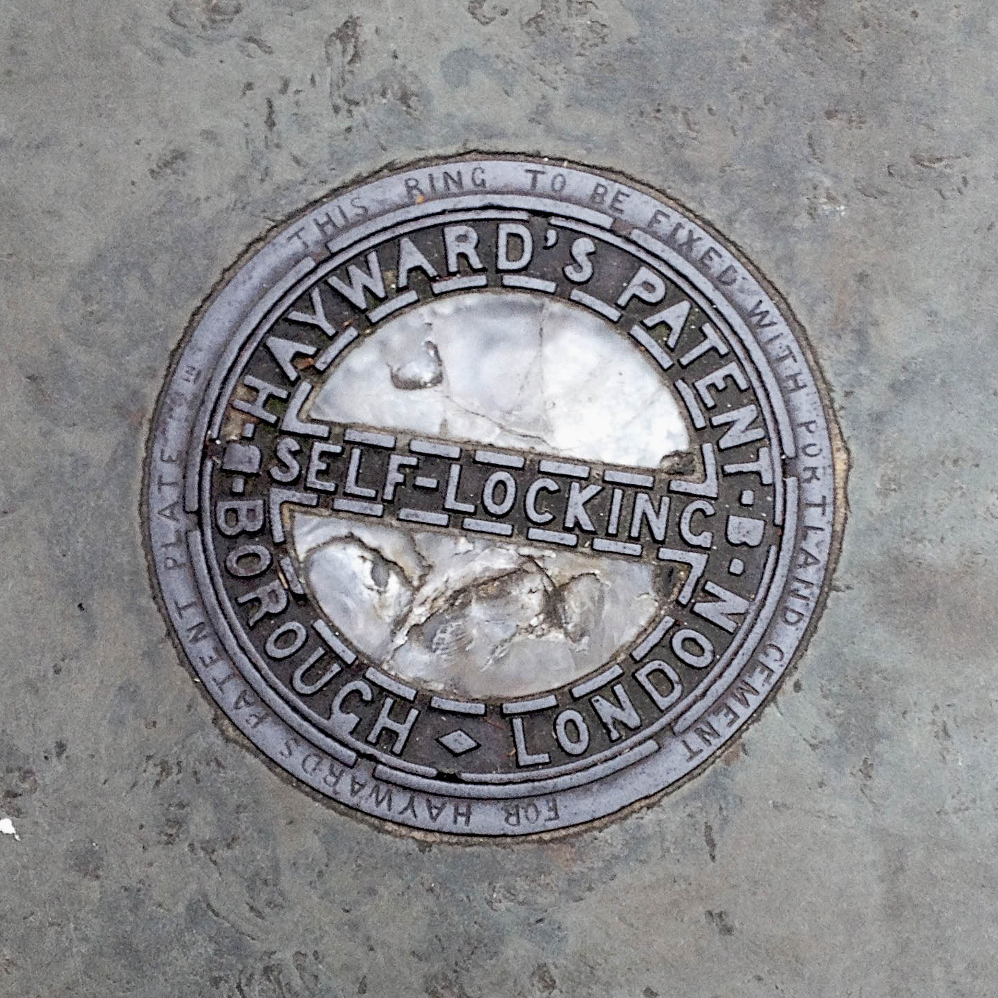 Manhole Cover, London - Cast iron surround inscribed with Hayward's Patent Borough London - Glass centre, divided by metal inscribed with Self locking