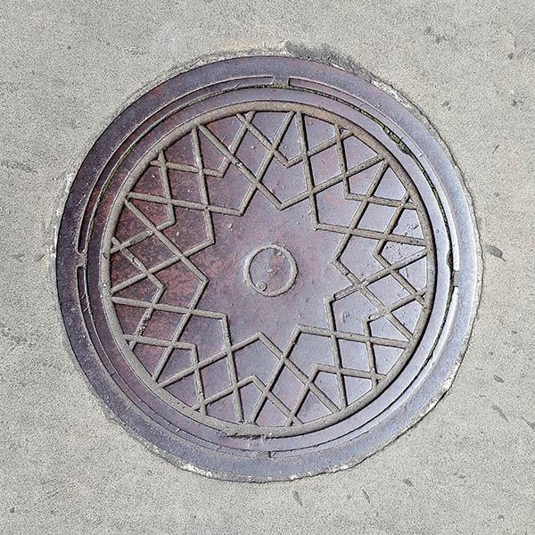 Manhole Cover, London - Cast iron surround with criss cross star pattern and circle