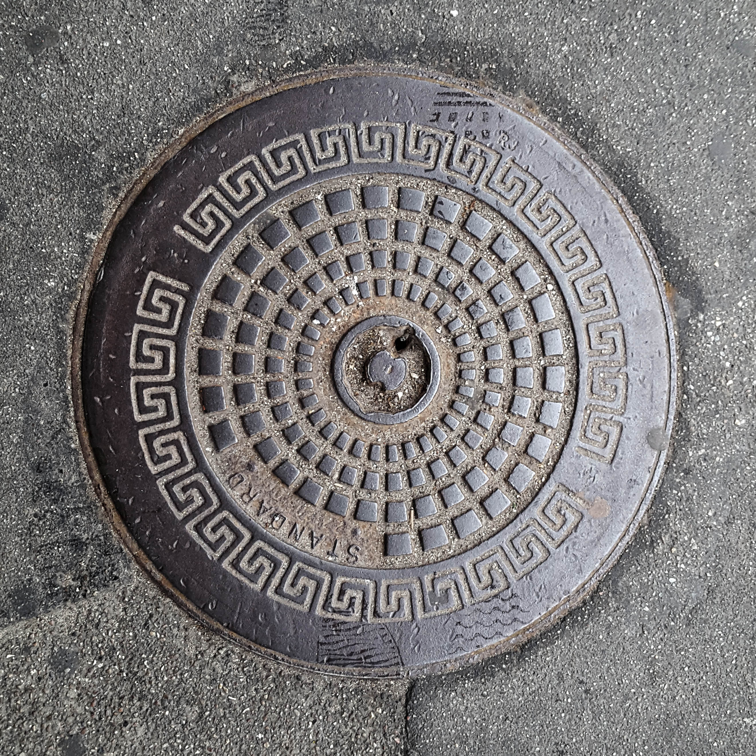 Manhole Cover, Frederiksvark Denmark - Cast iron surround with Greek key decorative border and inner pattern of concentric circles formed from graduated raised squares