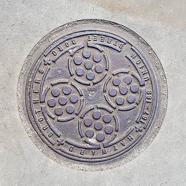 Manhole Cover, London - Cast iron surround inscribed with Hayward Brothers 187-189 Union Street Boro - Inner pattern of four circles surrounding smaller circles