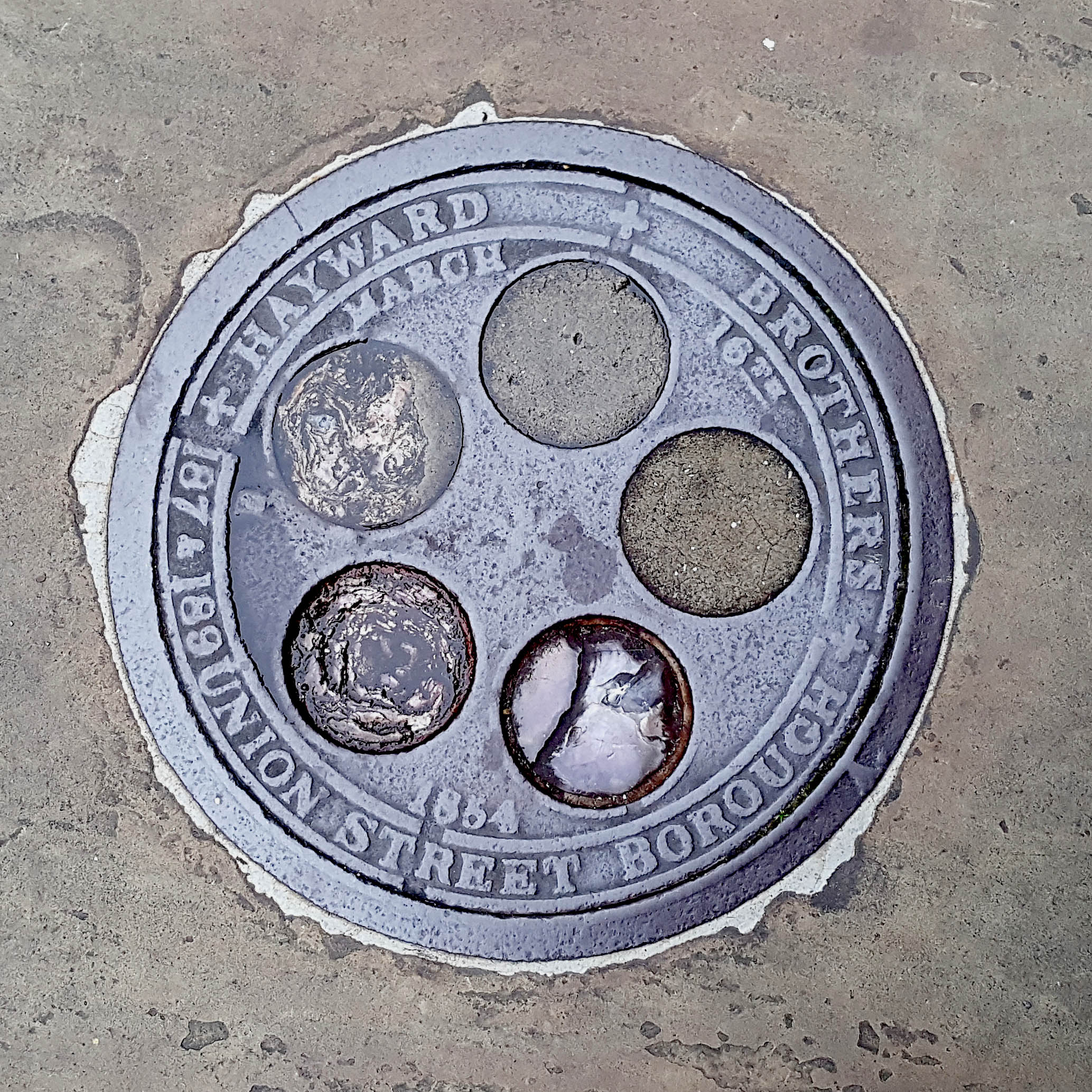 Manhole Cover, London - Cast iron surround inscribed with Hayward Brothers 187-189 Union Street Borough - Inner with five circles of concrete and glass