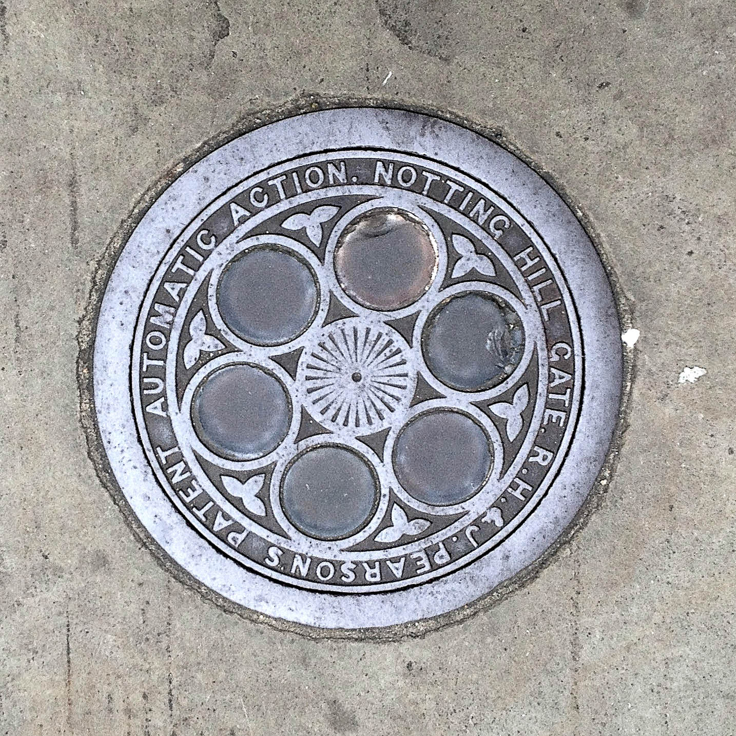 Manhole Cover, London - Cast iron surround inscribed with R H & J Pearson's patent Automatic Action. Notting Hill Gate - Inner, six glass circular inserts
