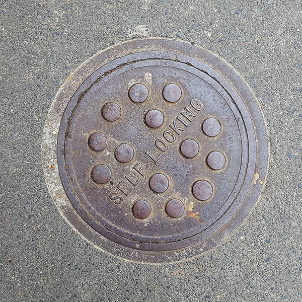 Manhole Cover, London - Cast iron with raised circle pattern and inscribed with Self Locking