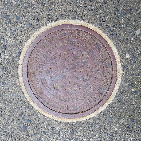Manhole Cover, London - Cast iron with worn away decorative pattern