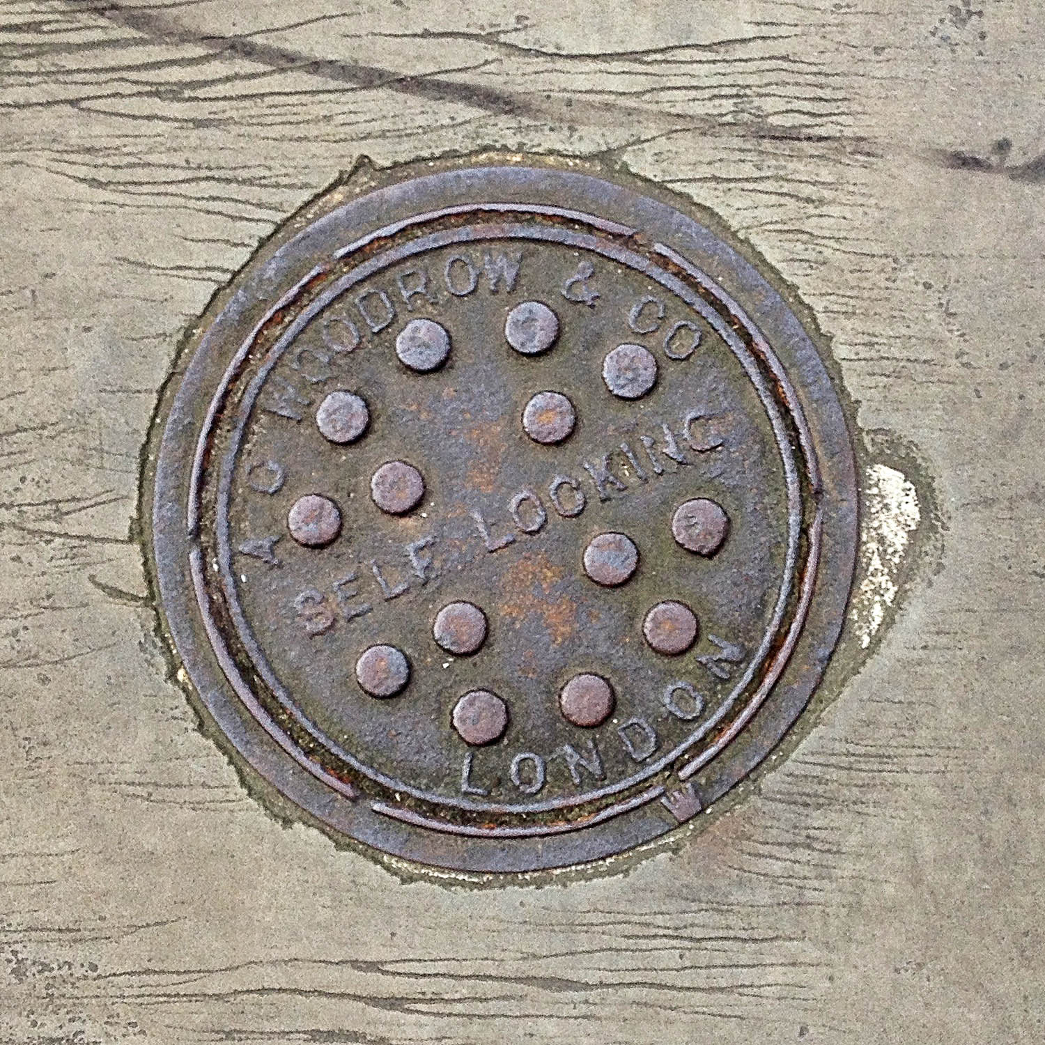 Manhole Cover, London - Cast iron inscribed with A C Woodrow & Co Self Locking London - 14 raised circles forming pattern