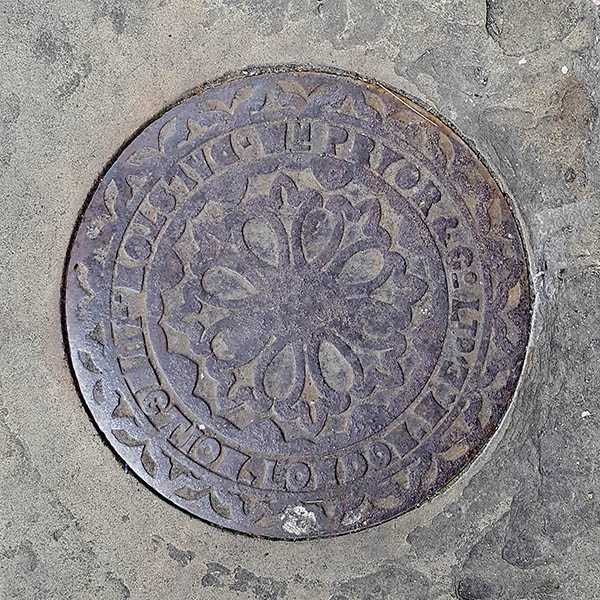 Manhole Cover, London - Cast iron with decorative circular fleur dis lis pattern - inscribed with WM Pryor & Co Ltd Dalston Junction London NE