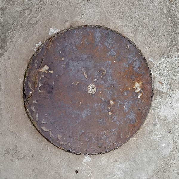 Manhole Cover, London - Cast iron worn and eroded with age