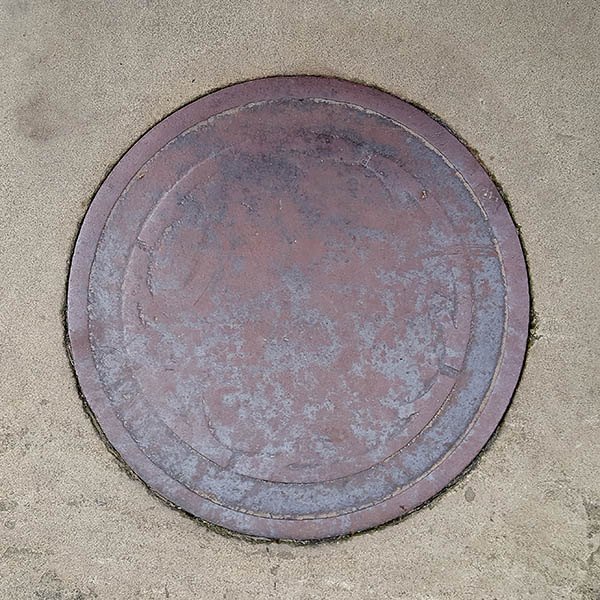 Manhole Cover, London - Cast iron worn with age