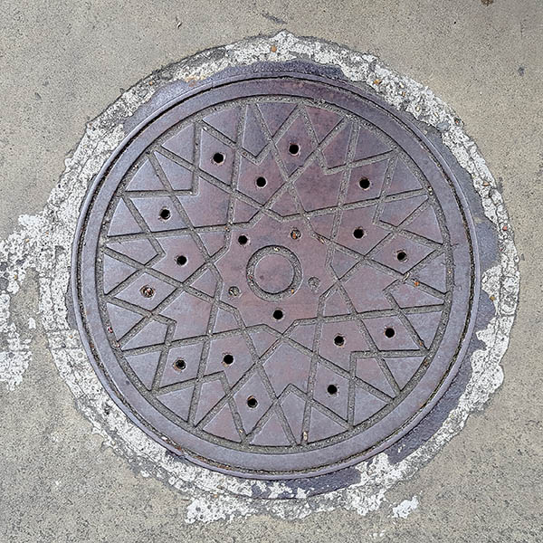 Manhole Cover, London - Cast iron criss cross star pattern with circle