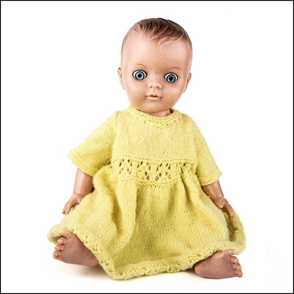 Vintage hard plastic doll with crazy eyes wearing a yellow knitted dress