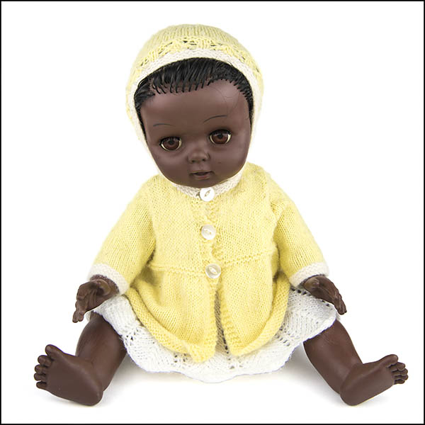 Vintage hard plastic doll wearing white knitted dress, yellow cardigan and bonnet