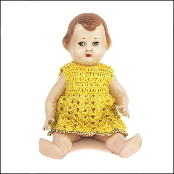 Vintage hard plastic doll wearing yellow knitted dress