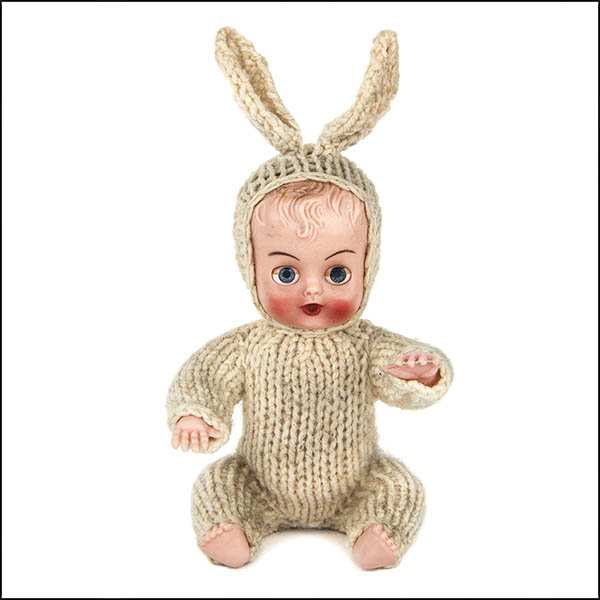Vintage hard plastic doll with beige knitted bunny outfit