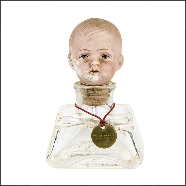 Vintage bisque doll's head stopper in clear glass ink bottle